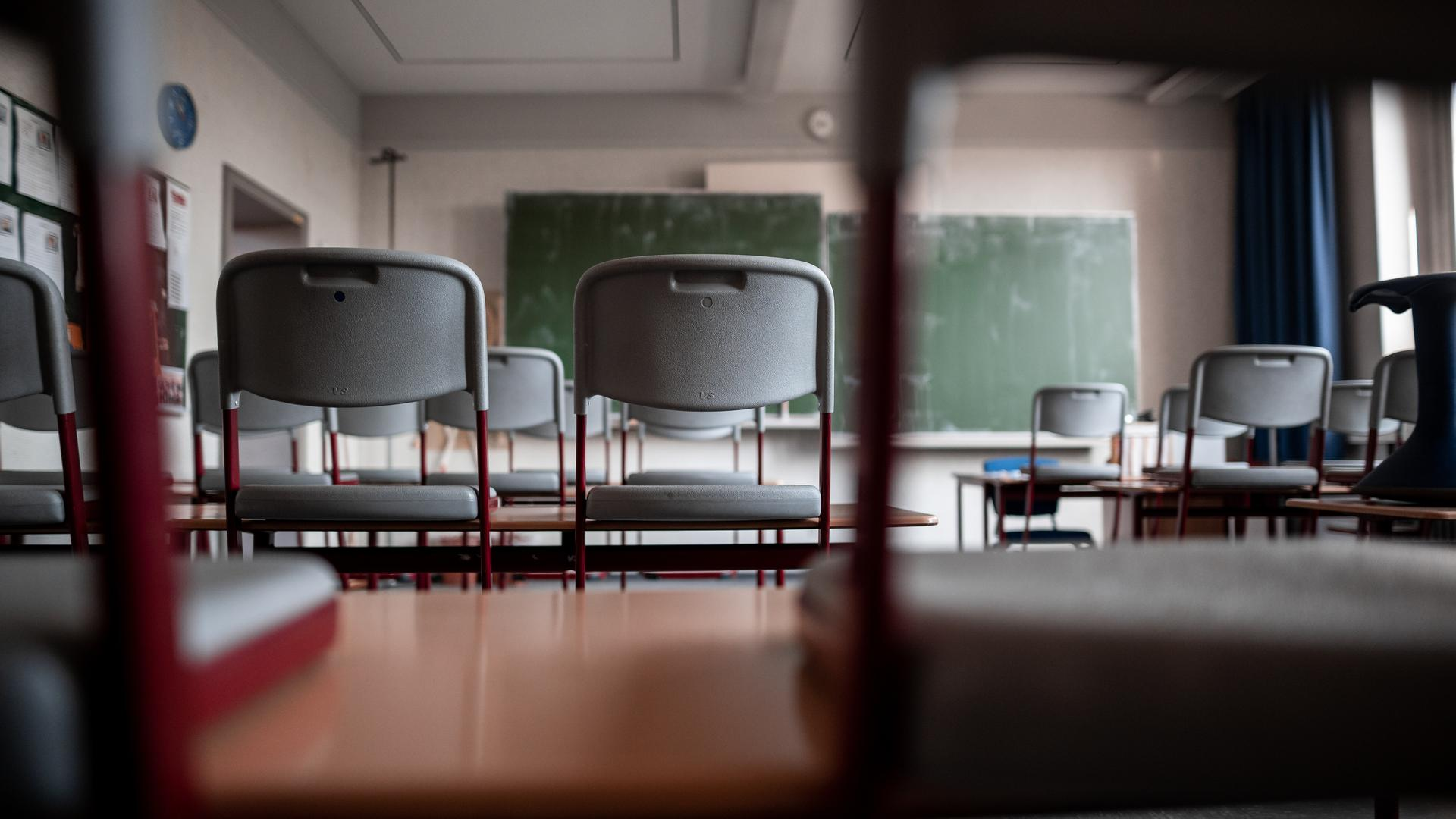 Stühle stehen auf den Tischen in einem leeren Klassenzimmer. +++ dpa-Bildfunk +++