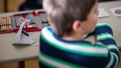 Eine FFP2-Maske liegt in einer ersten Klasse an einer Grundschule mit Wechselunterricht auf einem Tisch. Nach einem zweimonatigen Lockdown haben ab dem 22. Februar in mehreren Bundesländern wieder Schulen und Kitas unter bestimmten Hygienekonzepten geöffnet. So findet an Schulen zum Beispiel Wechselunterricht statt. +++ dpa-Bildfunk +++