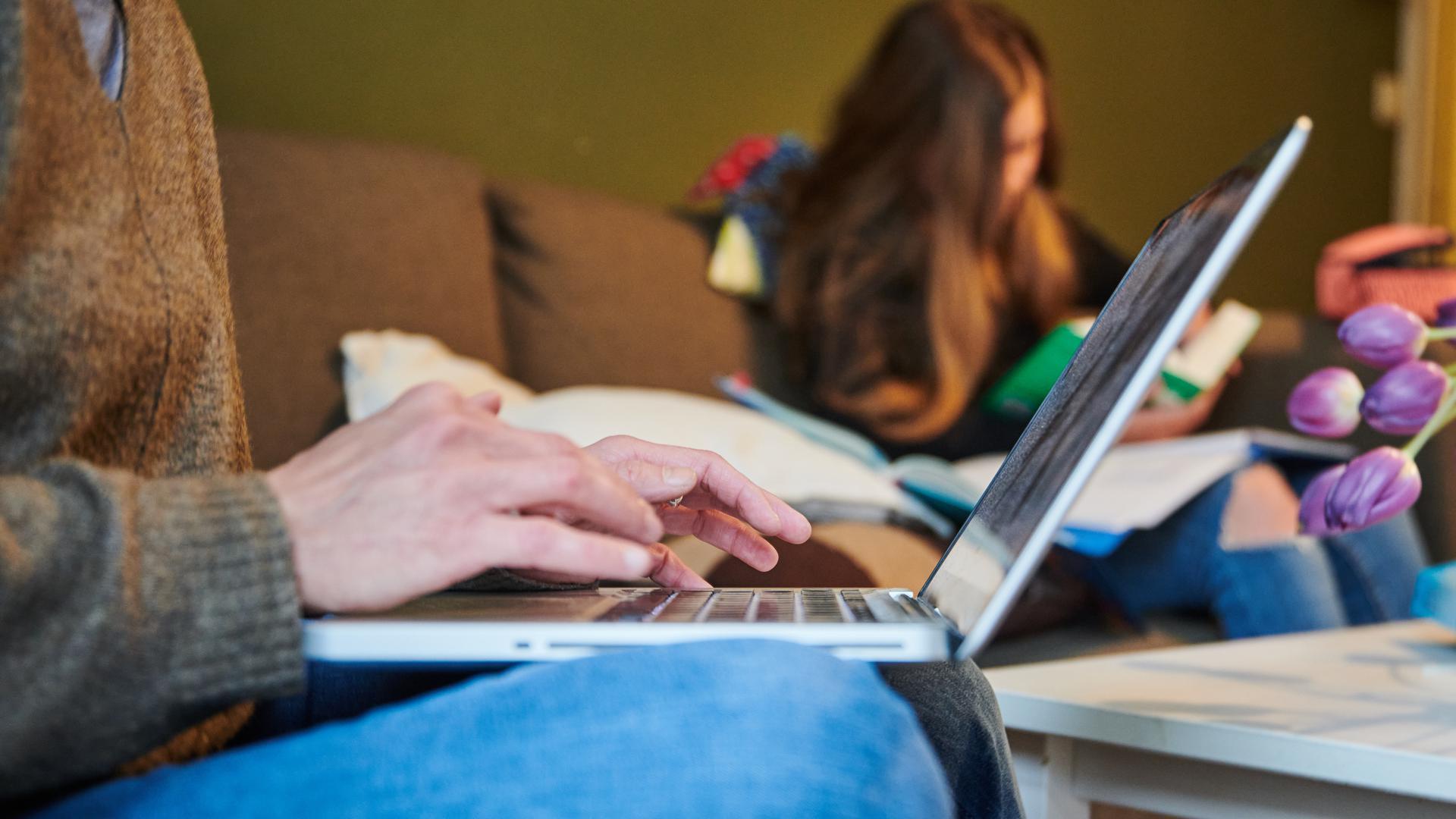 Eine Mutter arbeitet auf dem Sofa während ihre Tochter im Hintergrund in Schulhefte guckt. Wie ist die Situation von Frauen in der Corona-Krise? Verstärken sich in der Pandemie Geschlechterungleichheiten etwa bei Haushalt und Erziehung? +++ dpa-Bildfunk +++