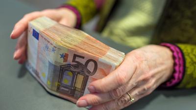 Eine Bank-Mitarbeiterin hält am Schalter einer Sparkasse in München 5000 Euro in 50-Euro-Scheinen in den Händen.