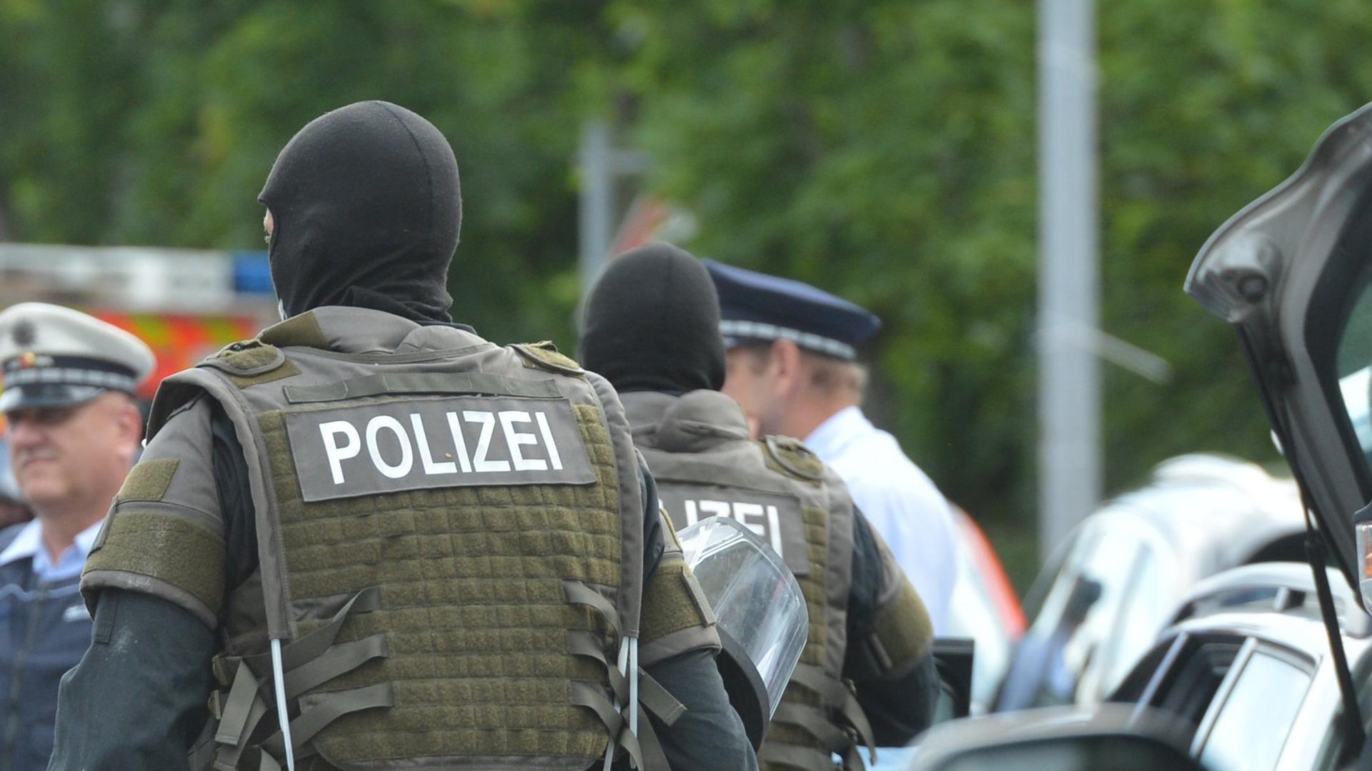 Polizisten eines Spezialeinsatzkommando laufen am 11.07.2016 in Stuttgart (Baden-Württemberg) zum Einsatzort. In Stuttgart hat ein Spezialeinsatzkommando der Polizei eine Kanzlei gestürmt. Dort seien zwei Männer tot im Keller gefunden worden, das teilte die Polizei am Montagabend mit. Foto: Franziska Kraufmann/dpa ++ +++ dpa-Bildfunk +++