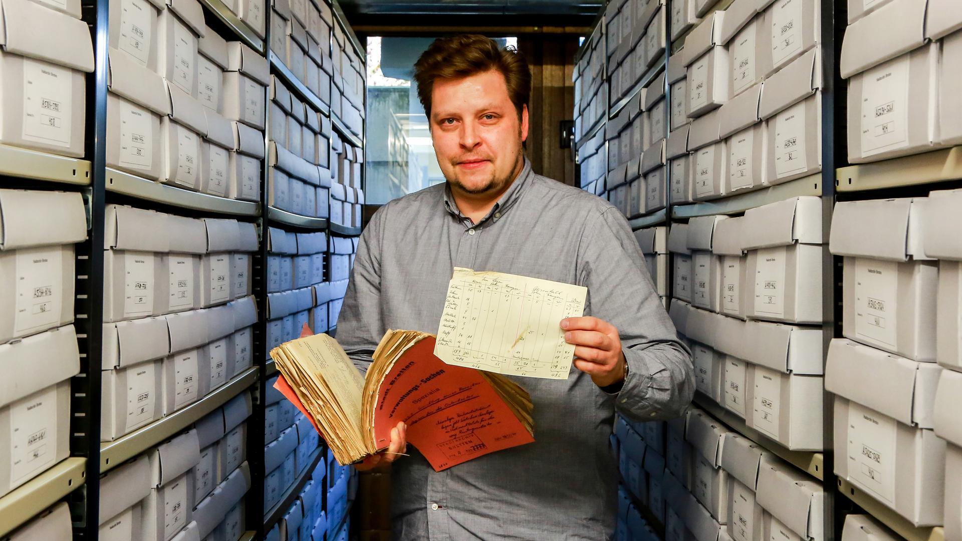 Mann mit Aktenbündel in Archiv