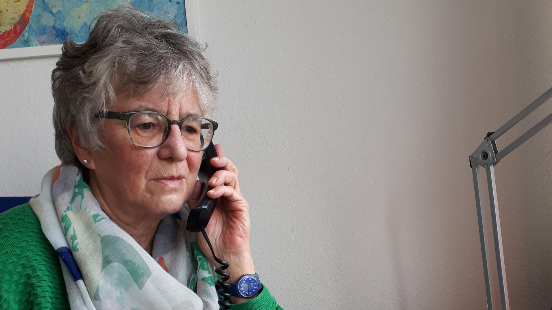 Bettina Grimberg, eine der Leiterinnen der Telefonseelsorge Karlsruhe, hat das Telefon am Ohr.