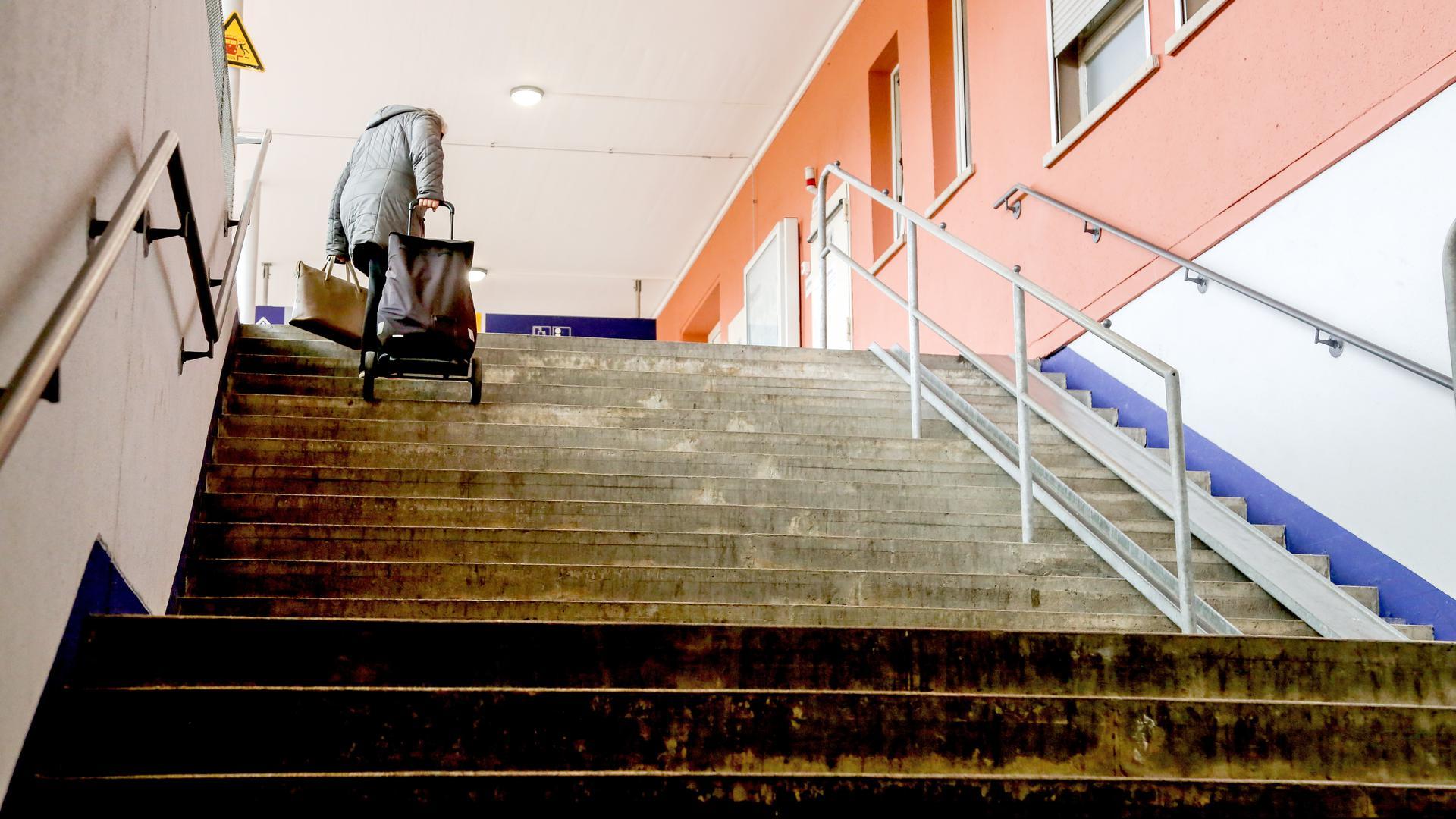 Frau mit Rolli auf Treppe