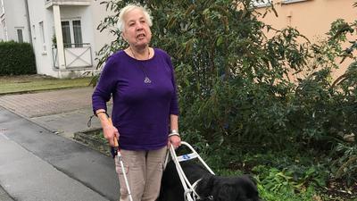 Eine blinde Seniorin mit ihrer zottelig-schwarzen Hundedame, einem Flat Coated Retriever.