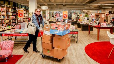 Eine Frau schiebt einen Wagen, der mit Kartons voller Bücher beladen ist. Im Hintergrund ist ein Buchladen zu sehen.