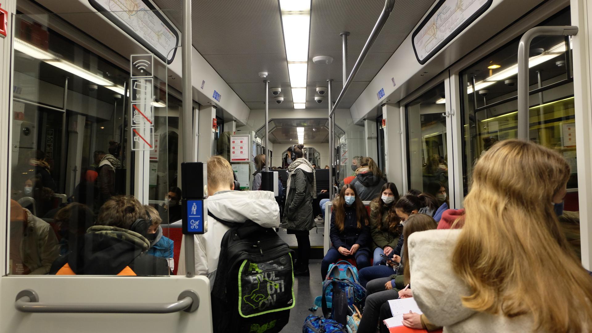 Junge Leute mit Masken in Zugabteil