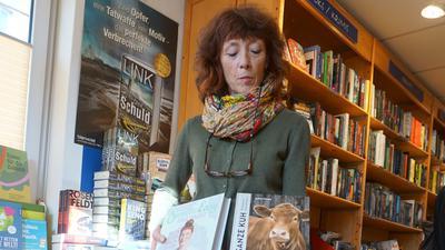 Frau steht mit Büchern in der Hand in Buchhandlung