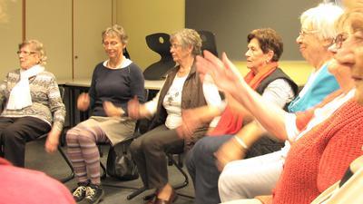 Seniorinnen sitzen im Kreis und bewegen sich.