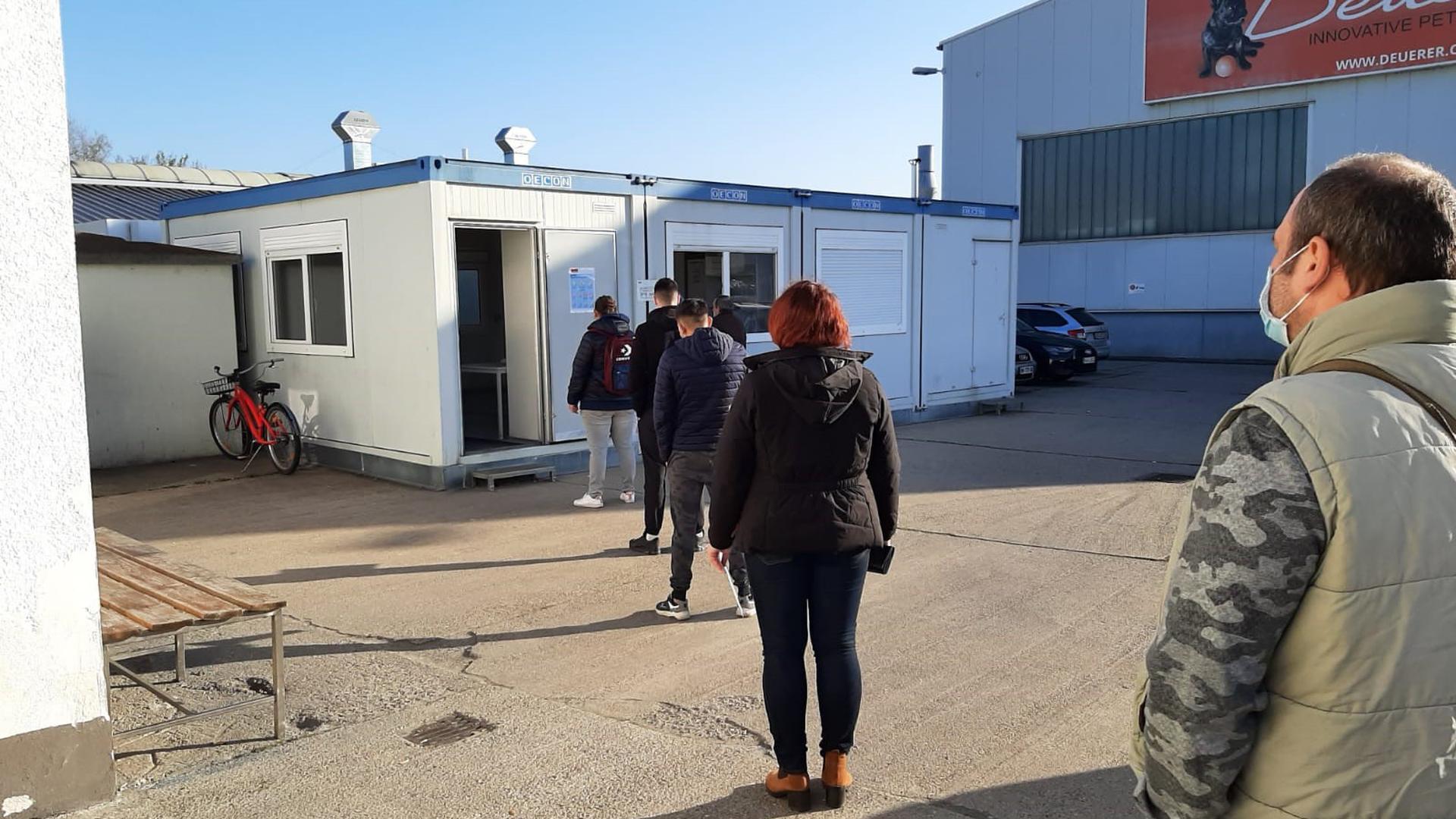 Männer und Frauen stehen vor einem Container an.