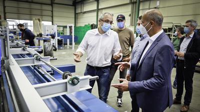 Geschäftsführer Carlo Sicko (links) und Dr. Markus Seiler (rechts) von der Invstmentfirma Finexx stehen an einer Keilzinkenmaschine.