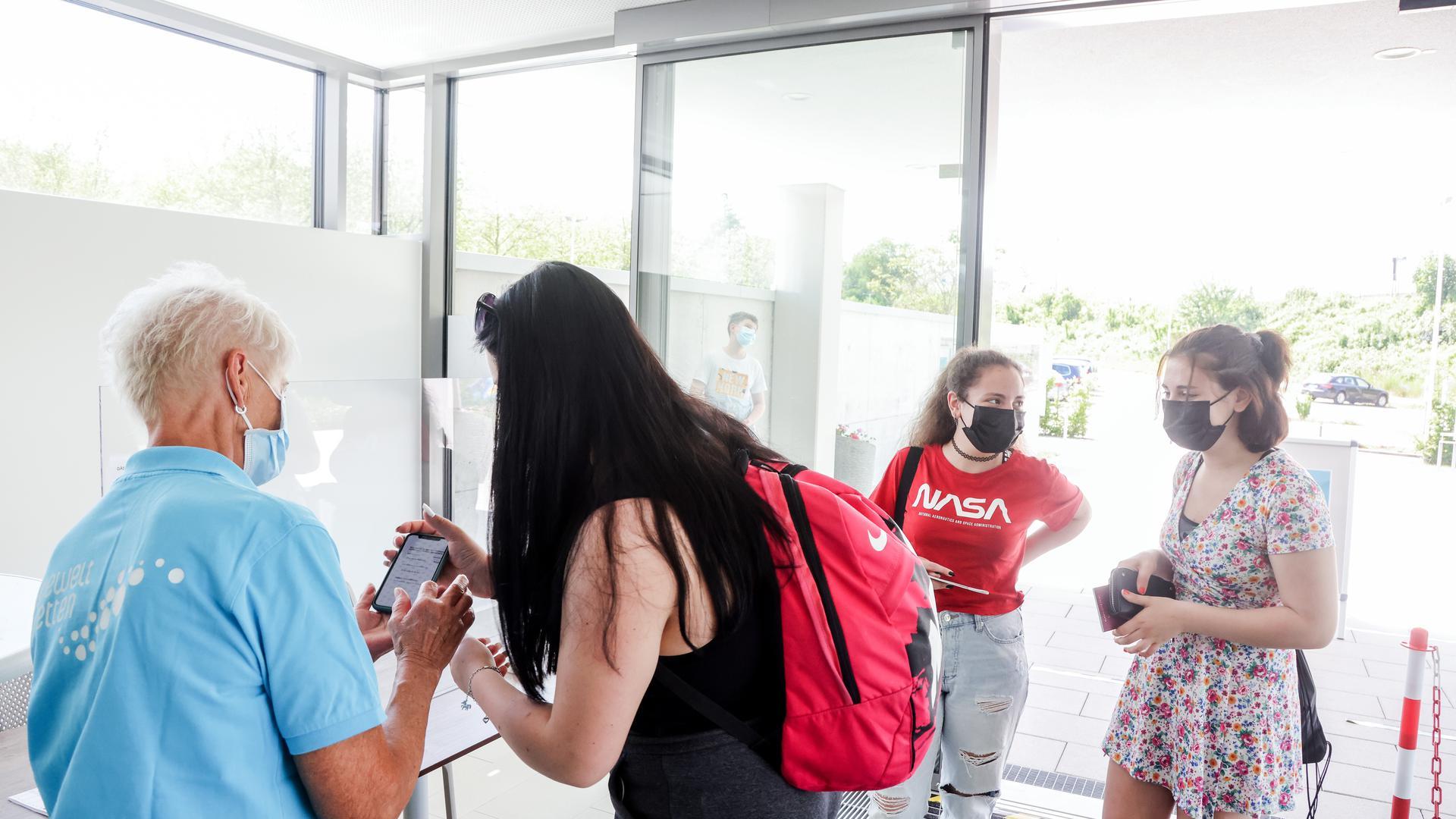 Drei Mädchen checken per Smartphone für die Badewelt ein.