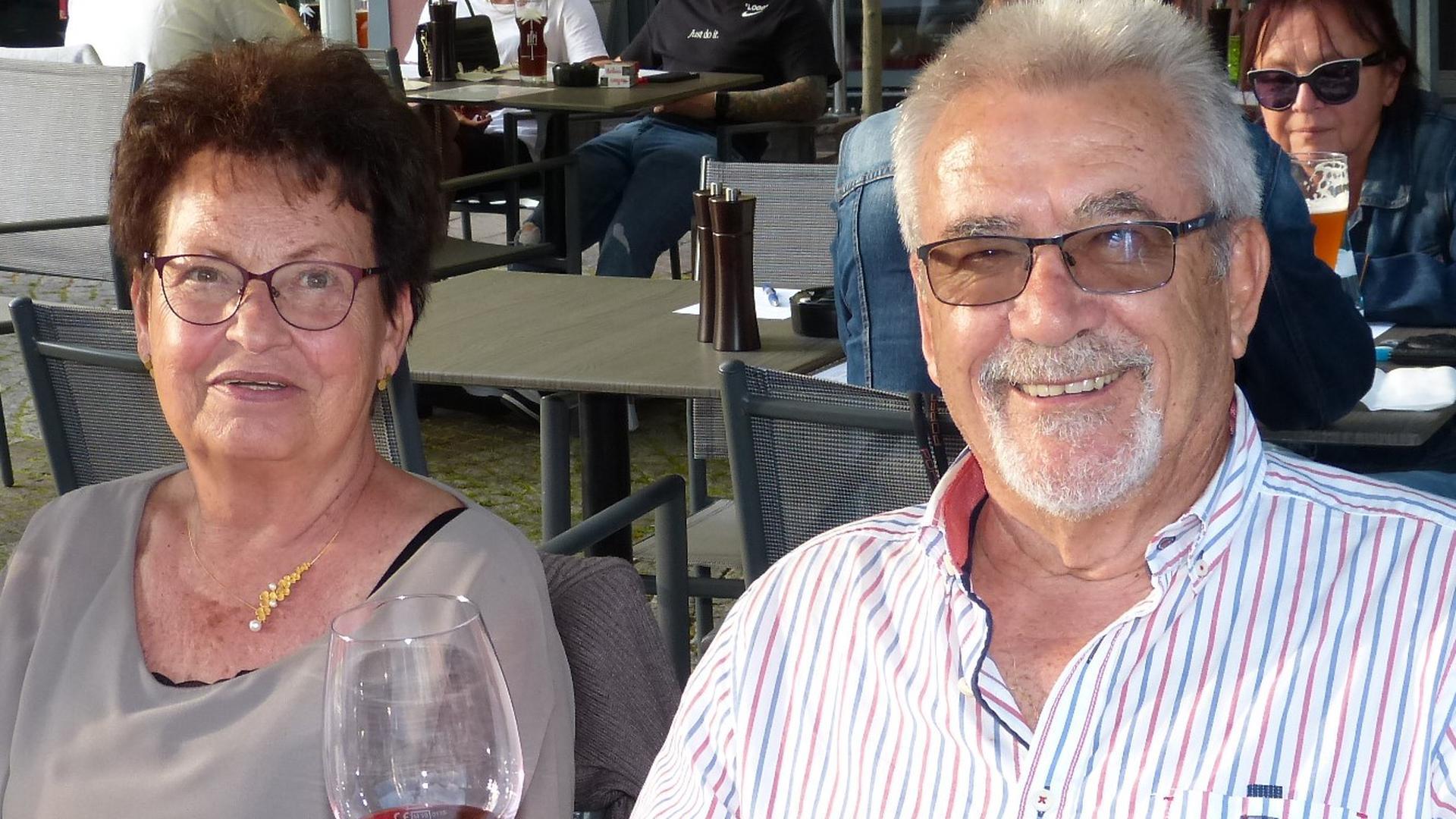 älterer Mann und Frau sitzen an Tisch in Außengastronomie, Mann hält Weinglas