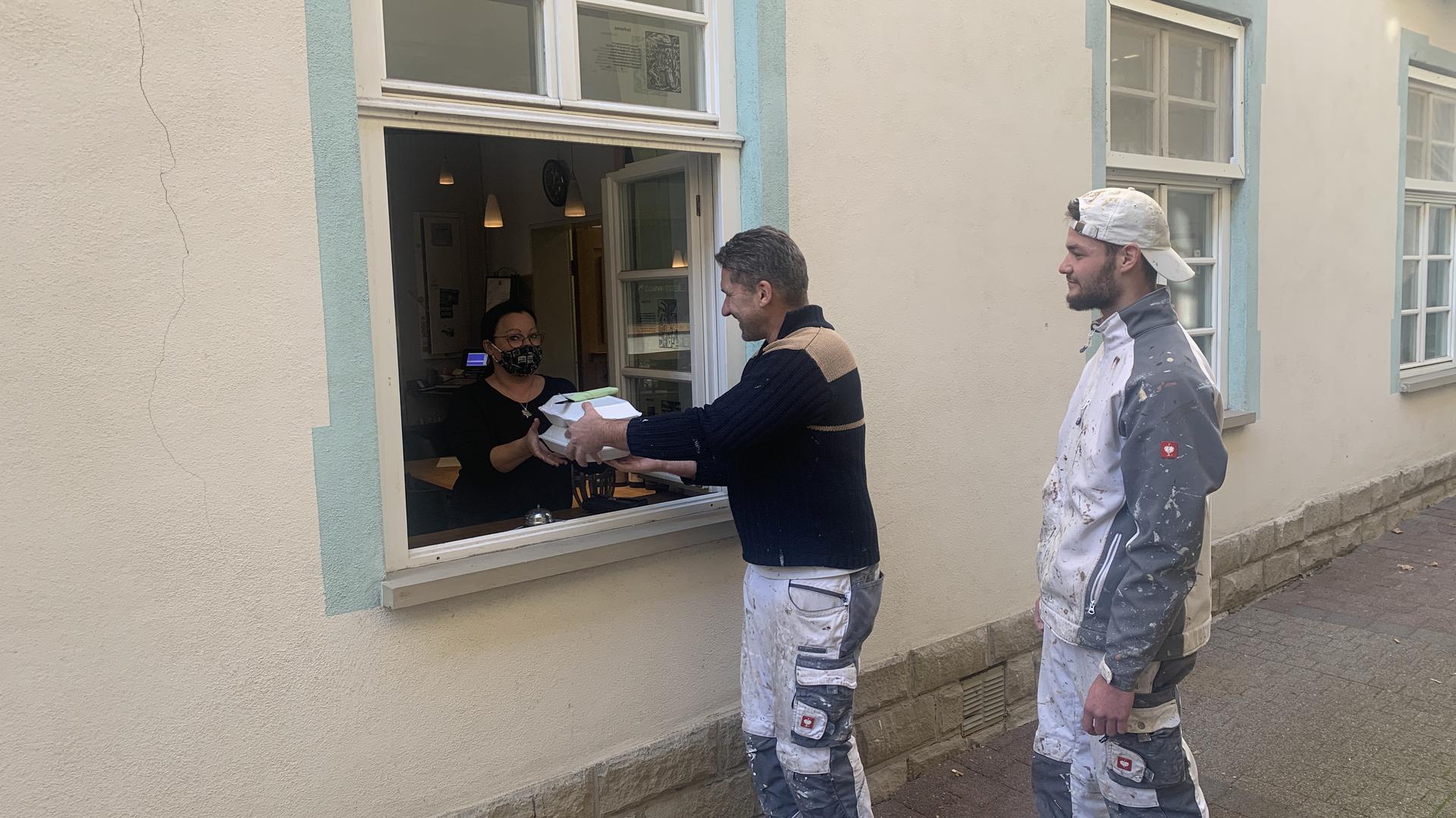 Nadja Oberdorfer (links) gibt zwei bestellte Essen durchs Fenster an die Kunden aus.
