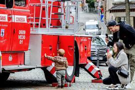 Kind und Eltern mit Feuerwehrfahrzeug