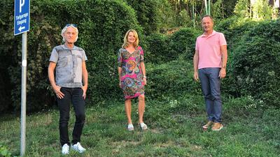 Drei Mitglieder der Gemeinderatsfraktion der Freien Wählervereinigung aus Bretten stehen vor einem begrünten Hang neben der Tiefgaragenausfahrt des Löwentors.