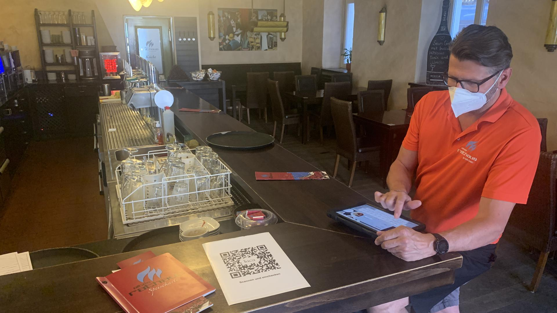Gastronom Ingo Jäger tippt am iPad Daten in die Luca App ein.