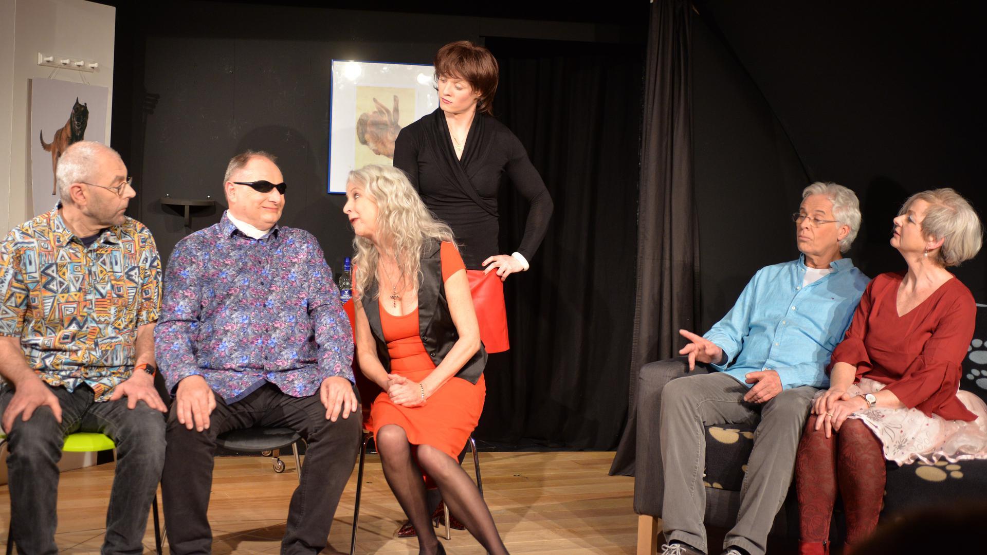 Sechs Personen in einer Theaterszene vor schwarzem Vorhang