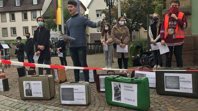 Junger Leute mit Koffern mit Namen und Bildern der Verschleppten