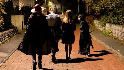 Gruselig kostümierte Jugendliche gehen an Halloween, dem 31. Oktober, durch die Nacht.
