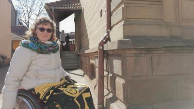 Frau im Rollstuhl vor Gebäude mit Treppe