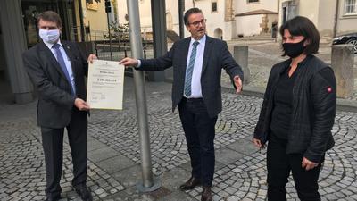 Zwei Männer, eine Frau mit Dokument