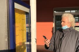 Mann mit Handy vor Fahrplan