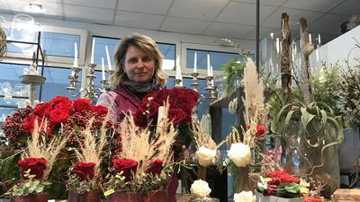 Stephanie Kreiter steht vor einem Stand mit Rosen in ihrem Blumengeschäft