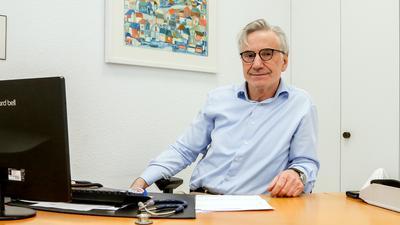 Ein Mann sitzt am Schreibtisch in seiner Praxis in Diedelsheim