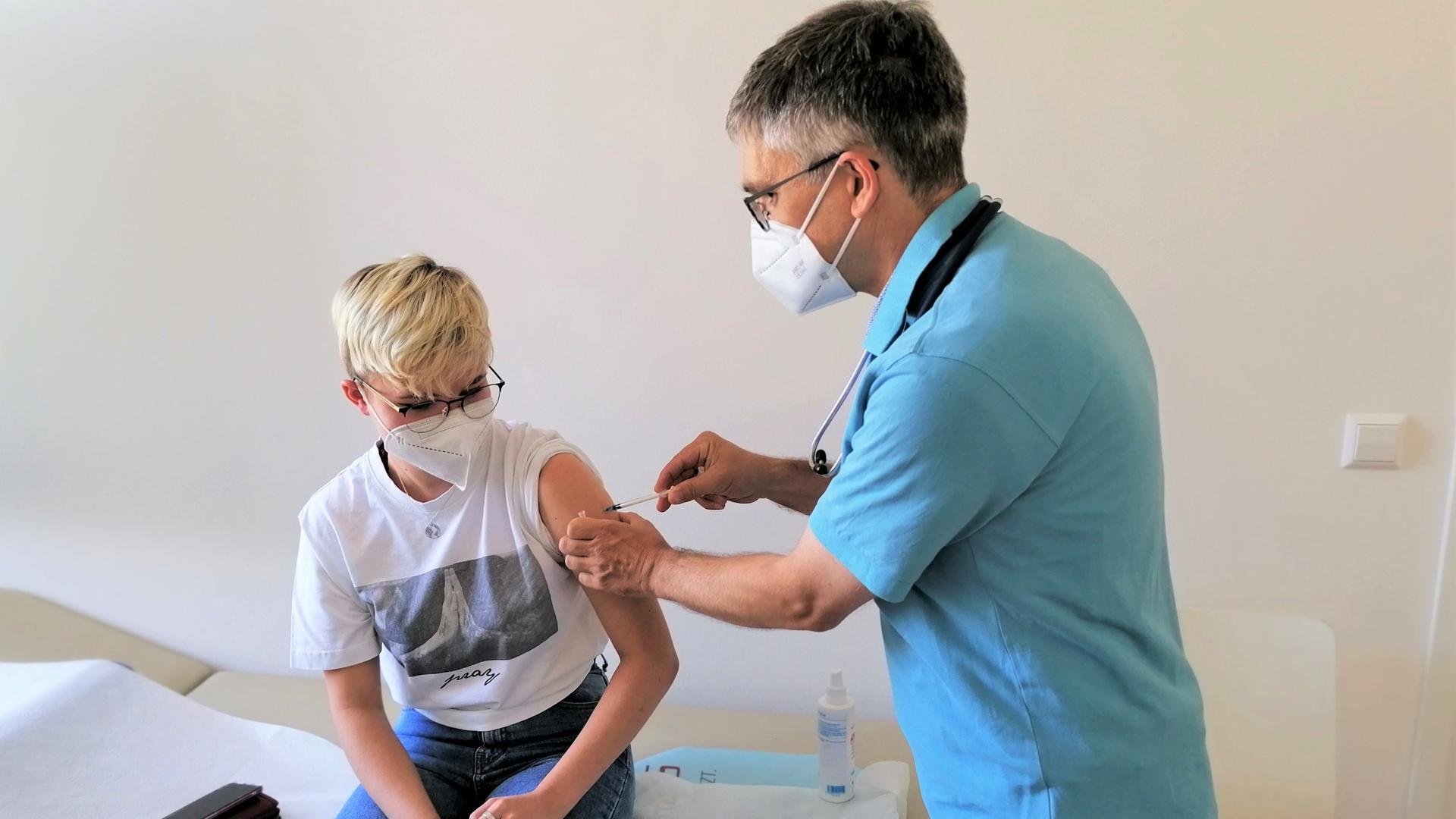 Mann impft ein junges Mädchen