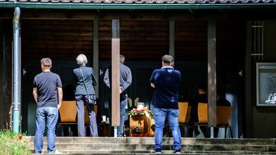 Menschen stehen auf dem Vorplatz einer Bestattungshalle