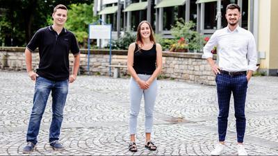 Junge Frau mit zwei jungen Männern zu ihrer linken und rechten Seite