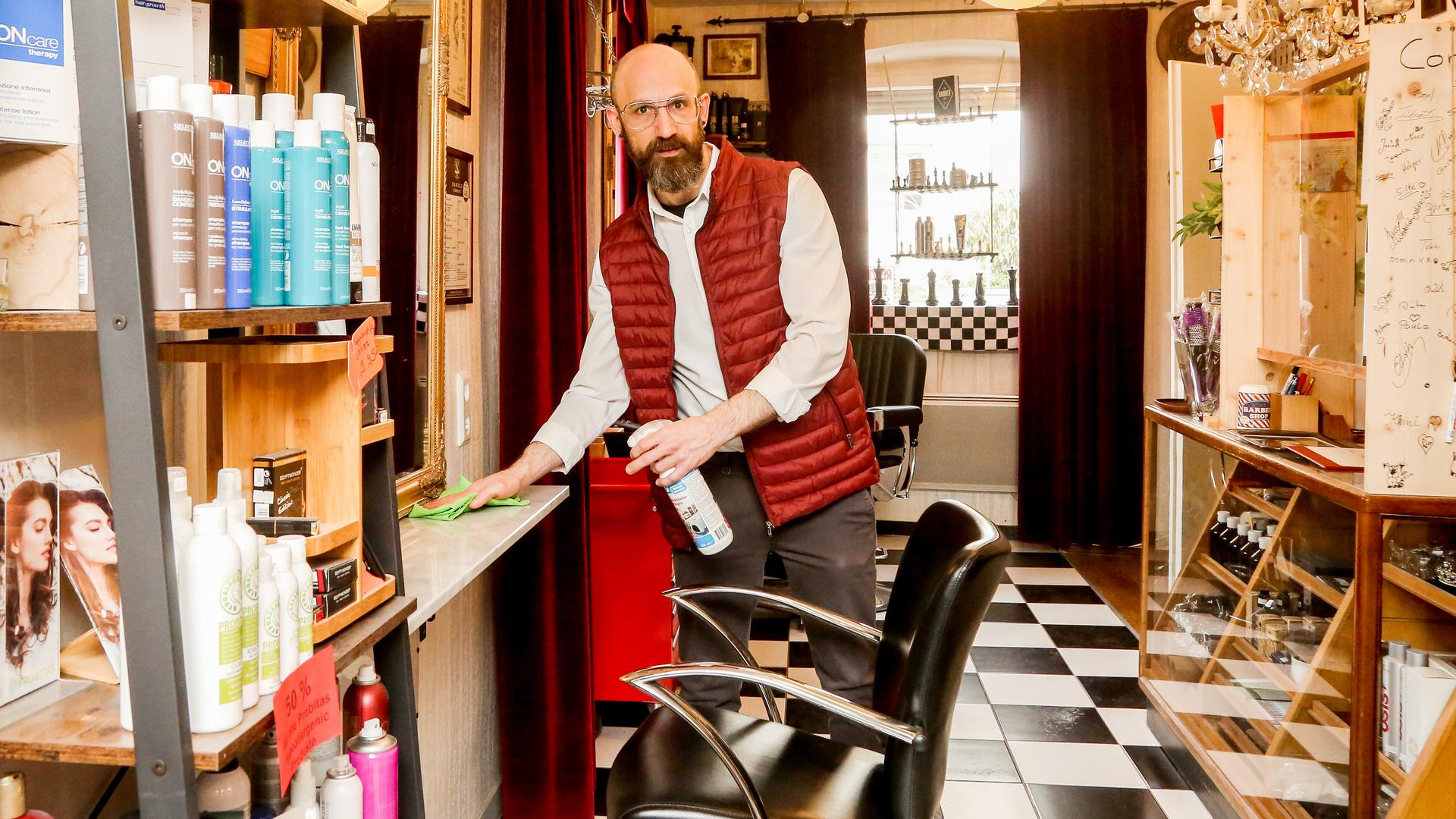 Daniel Simmel desinfiziert die Sitzplätze in seinem Friseursalon in Bretten