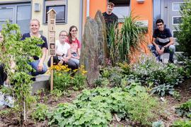 Gruppe von Jungen und Mädchen hinter einem Garten mit kleinem Insektenhäuschen