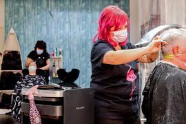 Jennifer Billeb schneidet einem Kunden die Haare. Im Hintergrund wäscht ihre Mitarbeiterin einer Kunden die Haare.