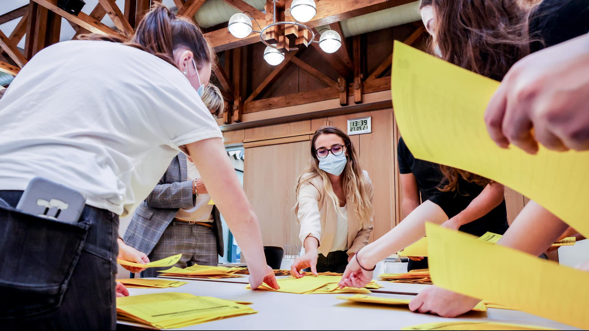Personen mit gelben Zetteln stehen um einen Tisch