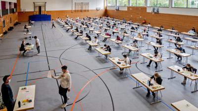 Mehrere Schüler sitzen an Schreibtischen in einer Sporthalle