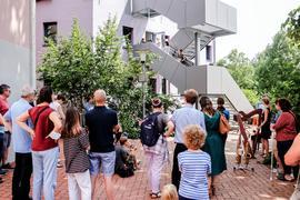 Menschen stehen um eine Treppe, auf der Kinder musizieren