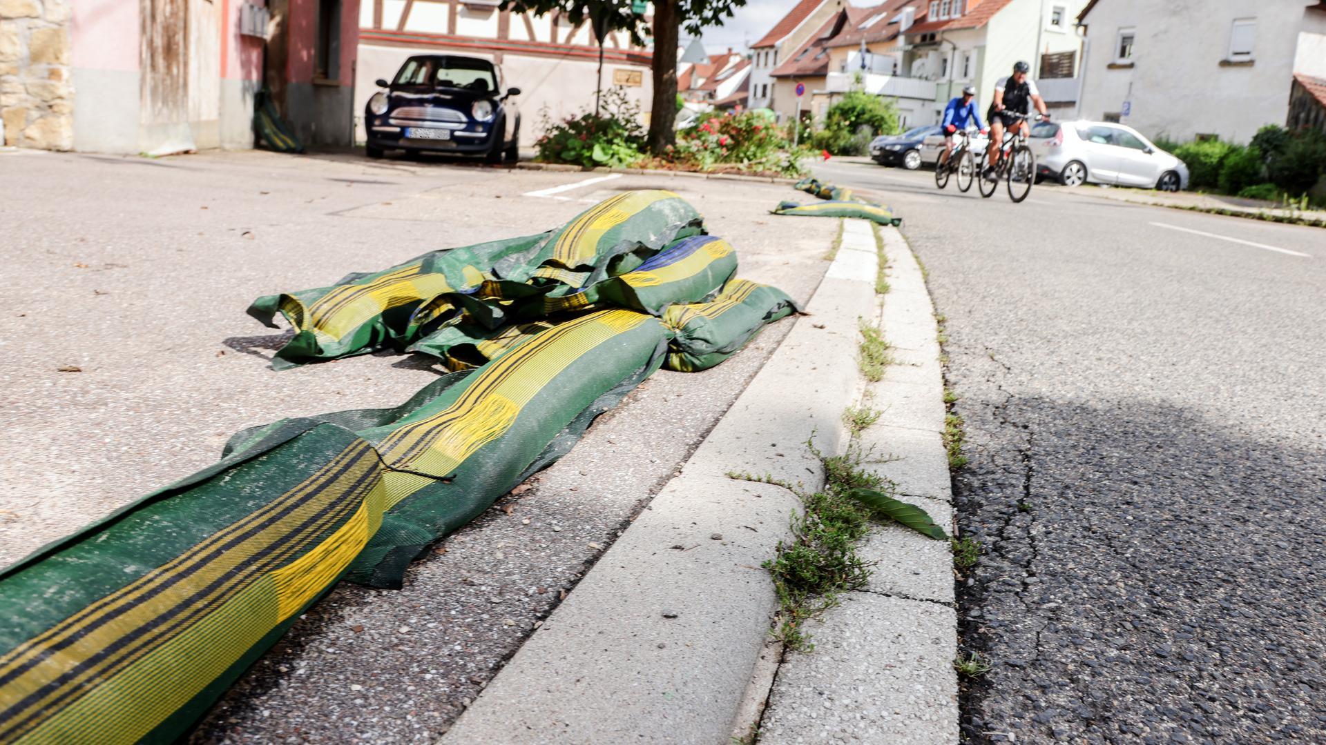 Im Brettener Stadtteil Ruit liegen am Tag nach der Überschwemmung noch Sandsäcke am Straßenrand.