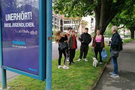 Mann mit einer Gruppe von Jugendlichen, Werbeplakat links im Bild