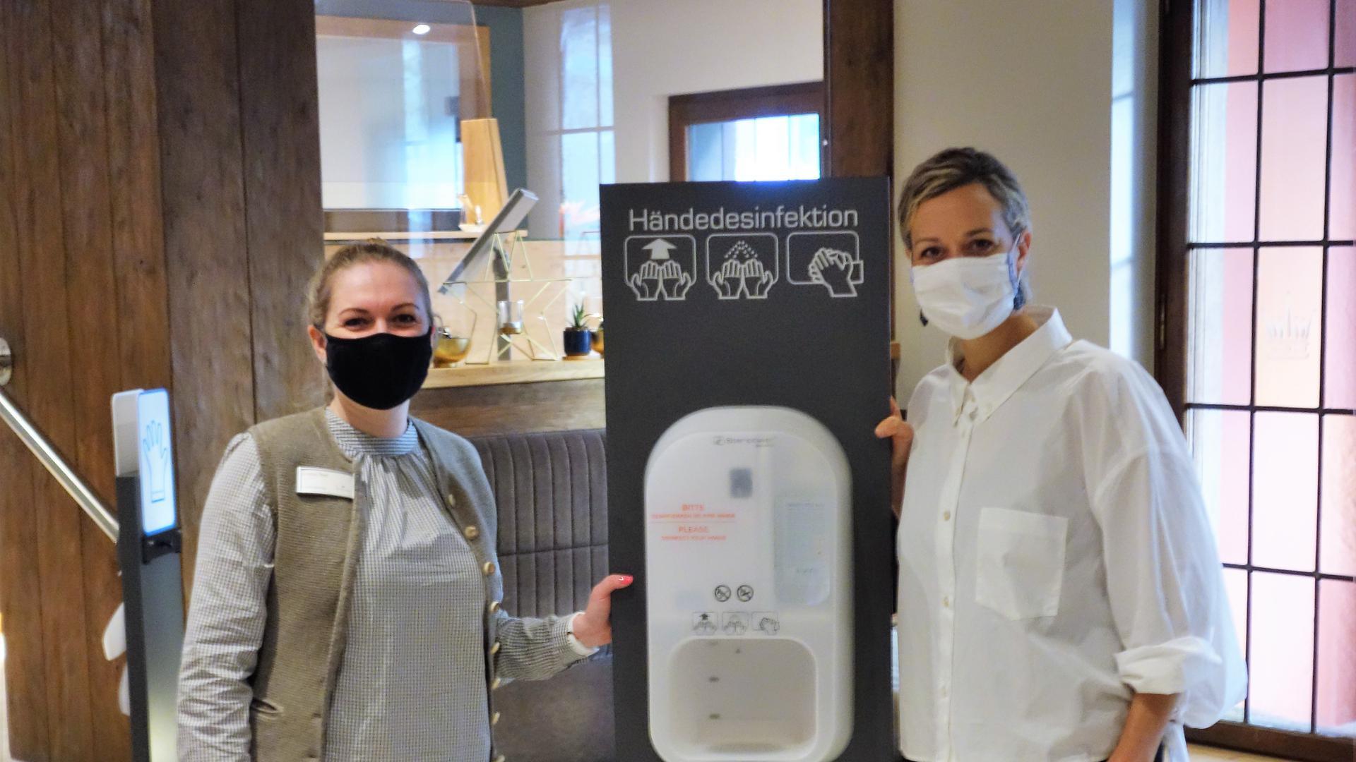 """Empfangsleiterin Karina Thal (l.) und Inhaberin Sabine Weishäupl im Ruhebereich des Einganges vom Hotel Krone mit einer """"Desinfektionsstation"""", wohl dem corona-typischen Bild dieser Tage."""
