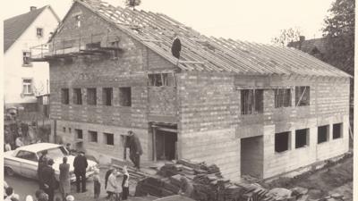 Das Bild zeigt den Kindergarten-Rohbau in Ruit von 1965. Auf dem Dach ist der damalige Ruiter Pfarrer Haas beim Richtfest zu sehen.