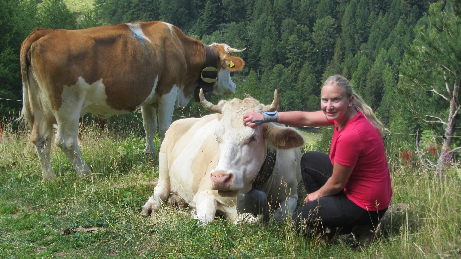 Laura Rübenacker zusammen mit zwei Kühen auf der Alpe Ginals.