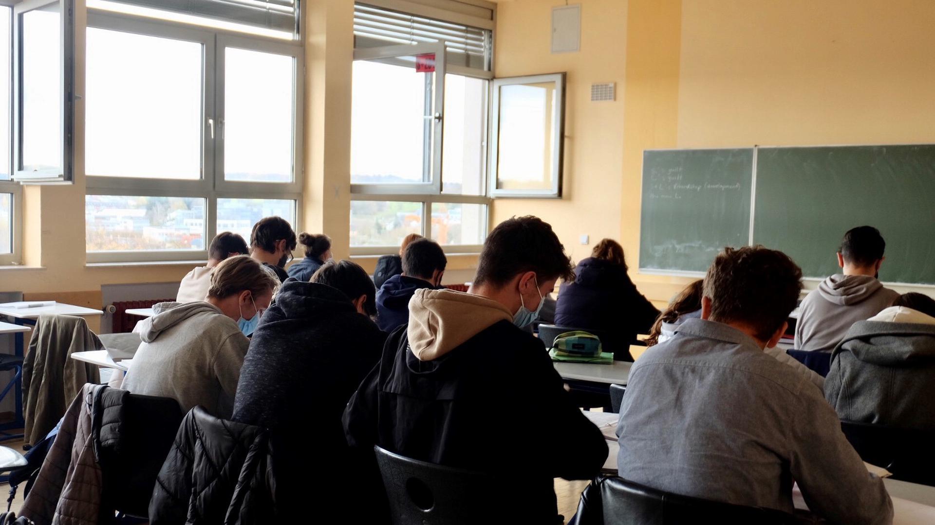 Schüler einer höheren Klasse sitzen bei geöffneten Fenstern an ihren Tischen.