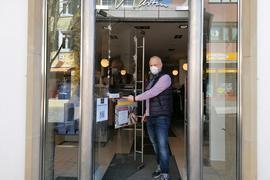 """Mann zeigt auf """"Click&Collect""""-Plakat an einer Eingangstür"""