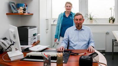 Arzt und Ärztin an Schreibtisch