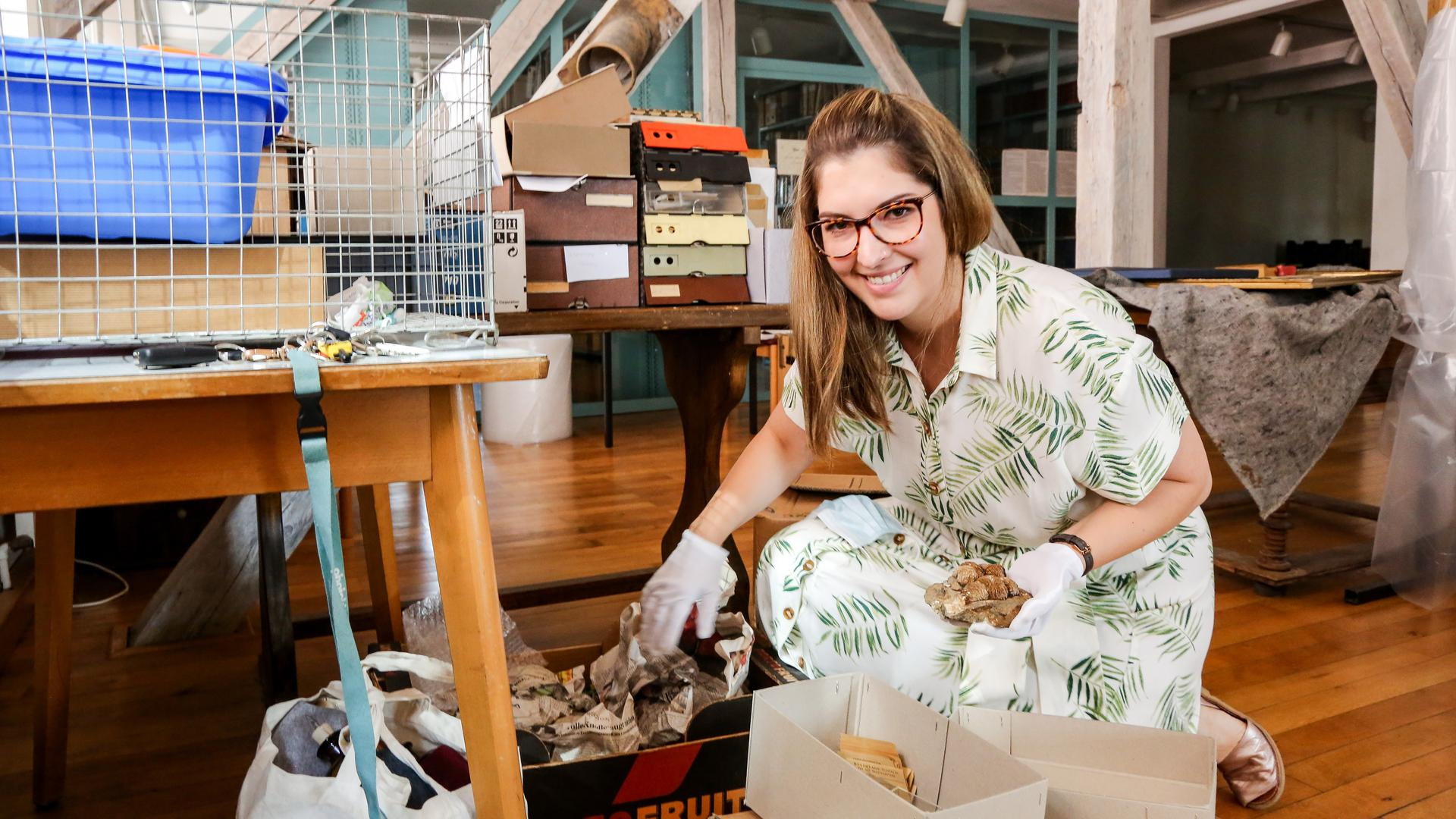 Museumsleiterin Linda Obhof kniet im Brettener Museumsdepot vor Kisten mit Mineralien.