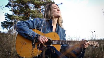 Caro Trischler sitzt mit ihrer Gitarre auf einer Wiese.