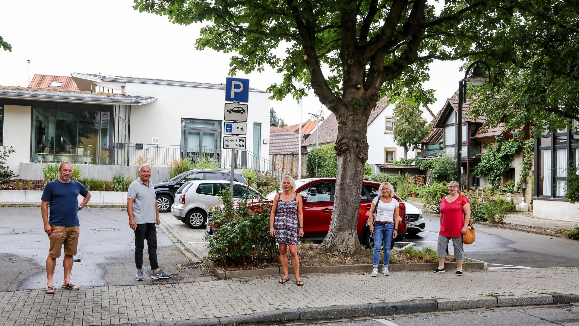 Zwei Männer, drei Frauen vor Parkplatz