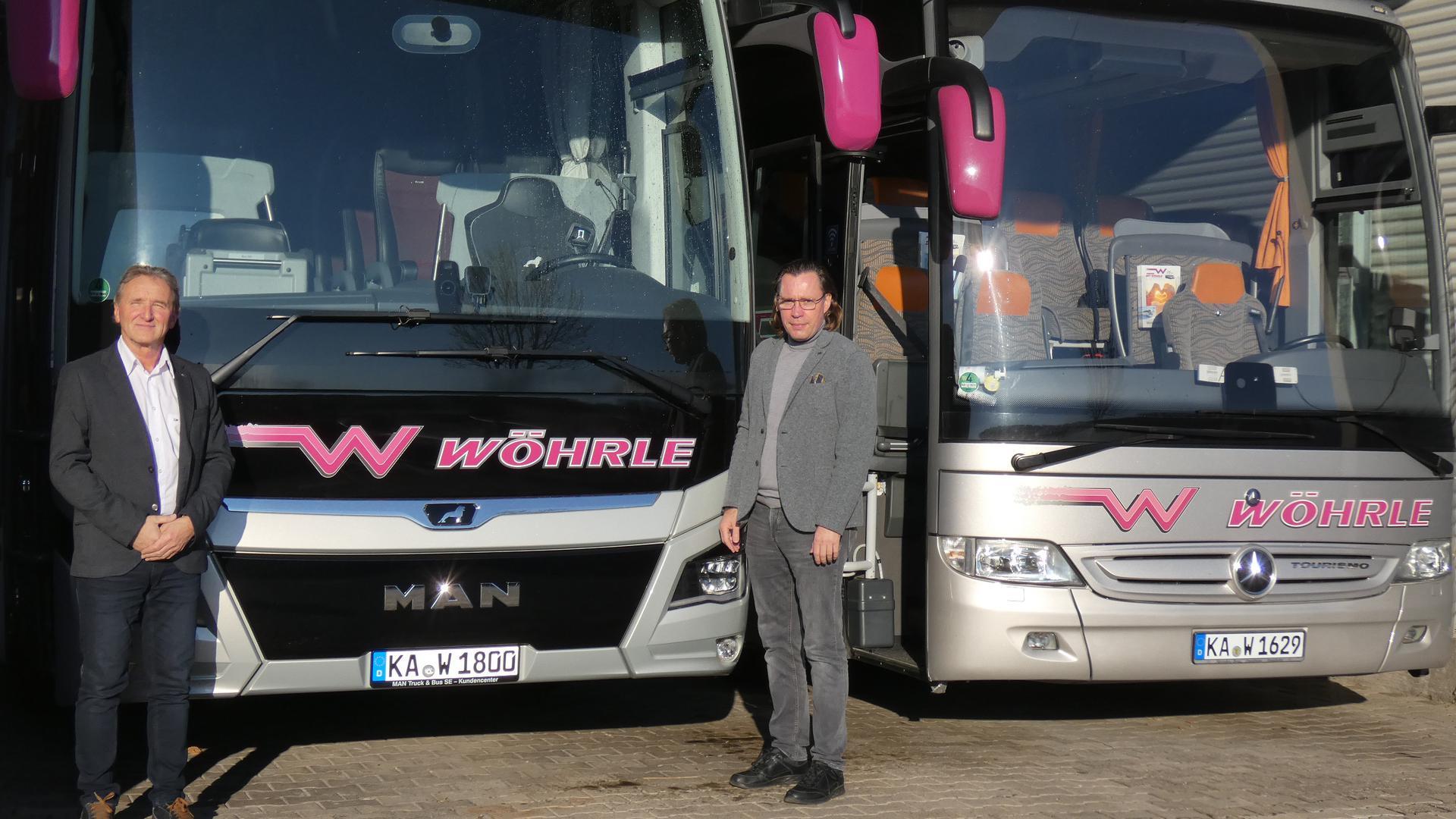 """Detlef Müller (rechts) und Thomas Balmer vor Reisebusen in der Halle in Oberderdingen. Müller ist bereits seit 1981 Busfahrer und seit 1989 bei der Firma Wöhrle beschäftigt. """"Jetzt wären wir eigentlich jedes Wochenende zu Skiausfahrten in die Berge unterwegs"""", bedauert er die Ausfälle."""